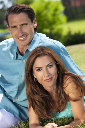Portrait shot of an attractive, successful and happy middle aged man and woman couple in their thirties, sitting together outside and smiling. photo