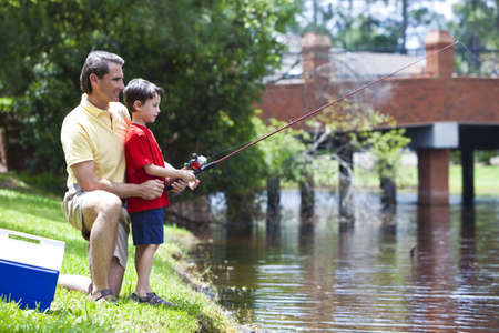 A father teaching his son how to fish on a river outside in summer sunshine Standard-Bild