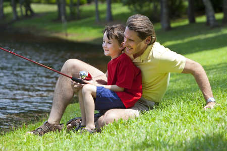 A father teaching his son how to fish on a river outside in summer sunshine Stock Photo - 7788516