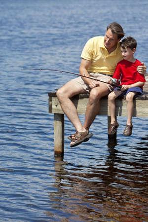 padre e hijo: Un padre que ense�ar a su hijo c�mo pescar en un r�o fuera de sol de verano  Foto de archivo
