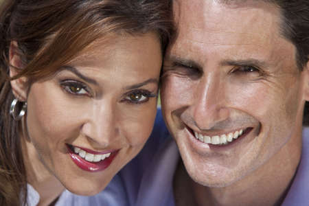 Close up portrait shot of an attractive, successful and happy middle aged man and woman couple in their thirties, sitting together outside  photo