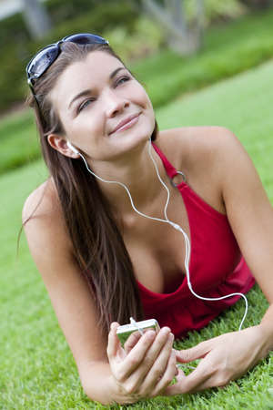 A beautiful young brunette woman lying down outside listening to music on her MP3 player photo