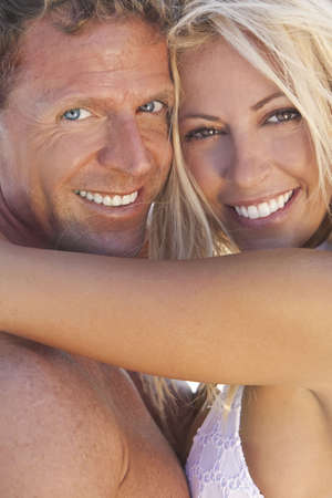 A sexy and attractive man and woman couple smiling and happy in the sunshine at the beach photo
