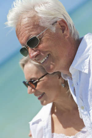 Happy senior man and woman couple together looking out to sea on a deserted tropical beach with bright clear blue sky photo
