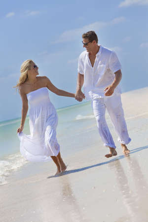 Happy young man and woman couple running, laughing and holding hands on a deserted tropical beach with bright clear blue sky photo