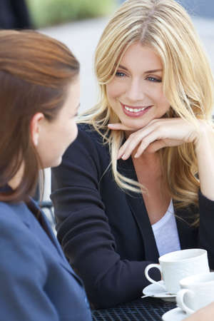 Two beautiful and sophisticated young women friends having coffee around a modern outdoor city cafe table Stock Photo - 7819012