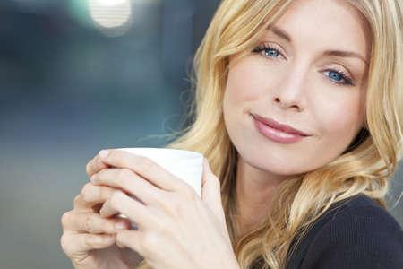 mujer tomando cafe: Una sonriente joven y bella mujer con cabello rubio y ojos azules, beber caf� o t� de una taza blanca  Foto de archivo