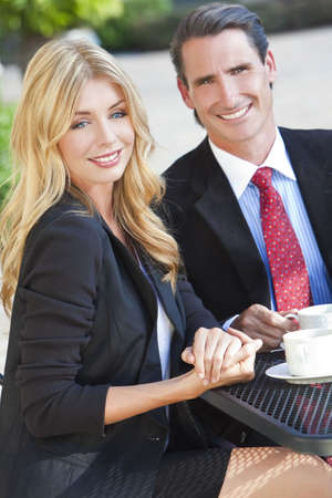 Beautiful woman & handsome man couple drinking coffee at outdoor cafe or restaurant table photo