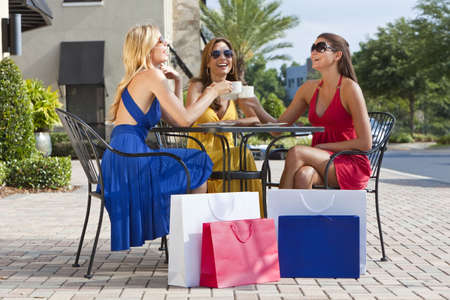 wealthy lifestyle: Three beautiful and sophisticated young women friends wearing sunglasses and having coffee around a modern city cafe table surrounded by shopping bags Stock Photo