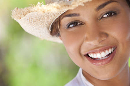 A beautiful ethnic mixed race young woman laughing and having fun wearing a straw cowboy hat, shot outside with a natural green background photo