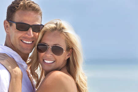 A and attractive man and woman couple smiling and happy wearing sunglasses in sunshine at the beach