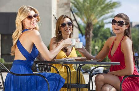 wealthy lifestyle: Tre giovani donne belle e sofisticati amici indossare occhiali da sole e avere caff� intorno a un tavolo di caff� della citt� moderna  Archivio Fotografico
