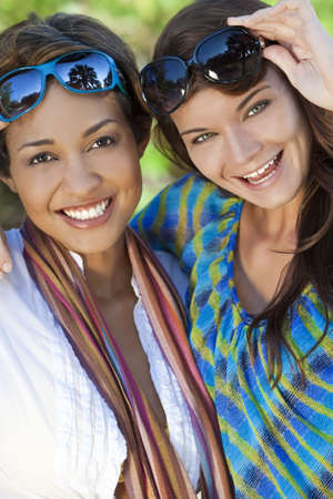 location shot: Two beautiful interracial young women in their twenties wearing sunglasses, laughing and having fun on vacation, shot in golden sunshine in a tropical resort location.