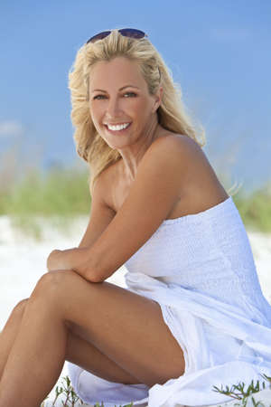 A beautiful young blond woman smiling in a white sundress sitting on a deserted tropical beach photo
