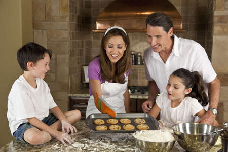 An attractive smiling family of mother, father, and two children baking and eating fresh chocolate chip cookies in a kitchen at home Stock Photo