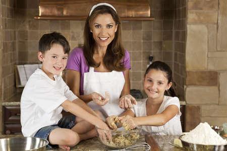 madre e hijo: Una atractiva sonriente madre, el hijo y la hija familia cocinar y hornear galletitas de chocolate en una cocina en el hogar  Foto de archivo