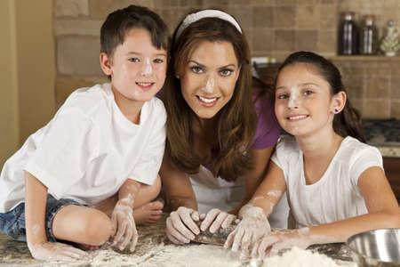 madre e hijo: Una atractiva sonriente madre, el hijo y la hija familia cocinar y hornear con harina y un rodillo en una cocina en el hogar