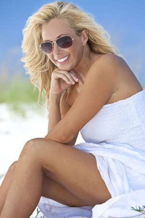 A beautiful young blond woman smiling in aviator sunglasses and a white sundress sitting on a deserted tropical beach photo