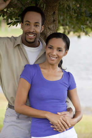 under a tree: A happy African American man and woman couple standing outside under a tree and holding hands. Stock Photo
