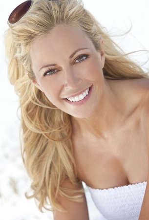 Una joven y bella rubia mujer sonriendo en gafas de aviador y una sundress blanca, sentado en una playa tropical desierta