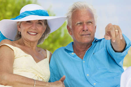 Happy senior man and woman couple sitting together pointing out to sea on a deserted tropical beach  photo