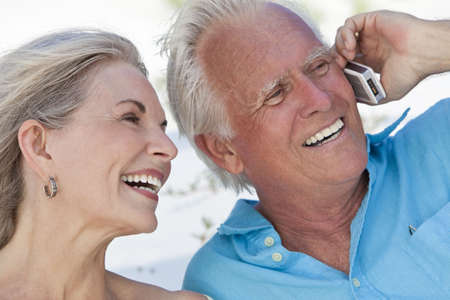 Happy senior man and woman couple laughing while talking on a mobile cell phone photo