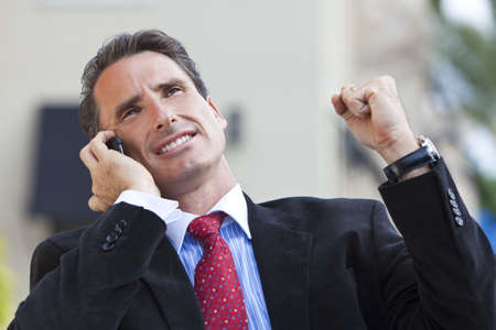 fist pump: A businessman with clenched fist pump celebrating success while talking on his mobile cell phone Stock Photo