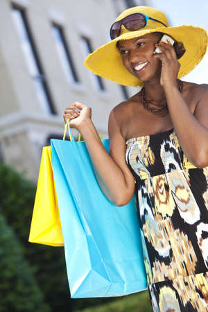 Beautiful and Fashionable African American woman with colorful shopping bags talking on her cell phone