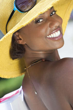 Beautiful happy, smiling and fashionable African American woman with colorful shopping bags wearing a big yellow sun hat photo