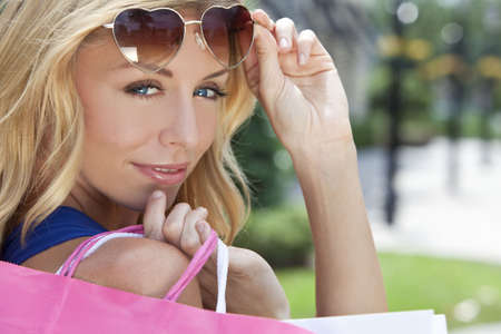 Beautiful, happy and fashionable woman with colorful pink and white shopping bags and wearing heart shaped sunglasses photo