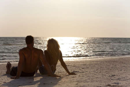 Rear view of a sexy and attractive young man and woman couple sitting on a beach looking out to see at sunset