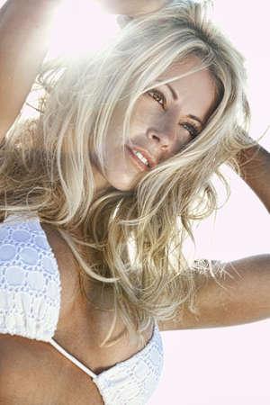Rango dinámico de alto, HDR, fotografía de una mujer rubia joven asombrosamente hermosa en iluminado por el sol y vistiendo un bikini blanco