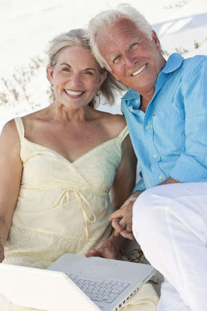Happy senior man and woman couple together using a white laptop computer on a beach. photo