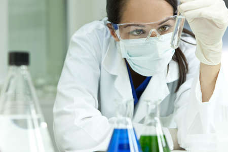 A female medical or scientific researcher or woman doctor looking at a test tube of clear solution in a laboratory with flasks in the foreground. Stock Photo