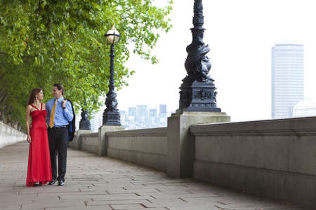 Romantic man and woman couple holding hands walking by the River Thames in London, England, Great Britain photo