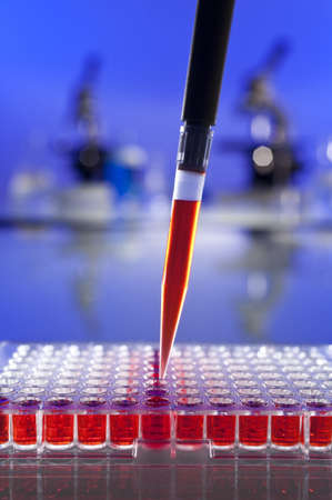 clinical laboratory: A pipette full of blood sample or red liquid and cell tray in a laboratory environment with microscopes and other equipment out of focus in the background