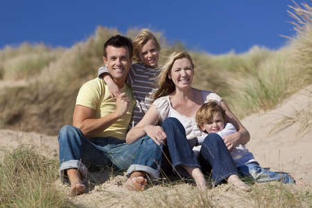 A happy family of mother, father and two sons, sitting down and having fun in the sand dunes of a sunny beach photo