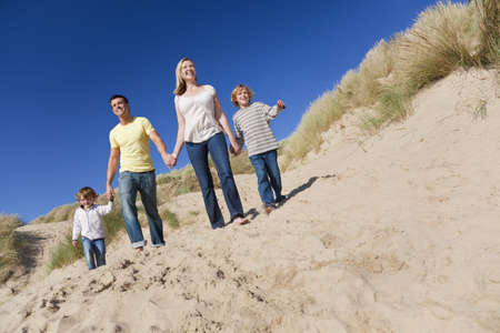 A happy family of mother, father and two sons, walking holding hands and having fun in the sand dunes of a sunny beach Stock Photo - 8005599