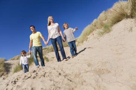 dune: Una familia feliz de madre, padre y dos hijos, caminando a manos de explotación y divertirse en las dunas de arena de una playa soleada