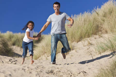 A man and young girl, father and mixed race daughter, running and having fun in the sand dunes of a sunny beach photo