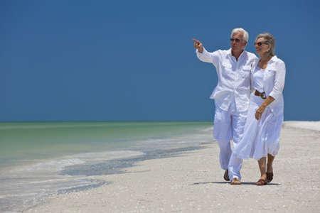 senioren wandelen: Gelukkige senior man en vrouw paar lopen samen op zoek naar zee op een verlaten tropisch strand met helder blauwe hemel, wijst de man naar de horizon
