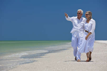 active holiday: Happy senior man and woman couple walking together looking out to sea on a deserted tropical beach with bright clear blue sky, the man is pointing to the horizon Stock Photo