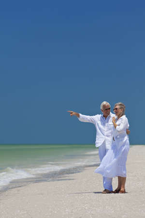 blue sky thinking: Happy senior man and woman couple together looking out to sea on a deserted tropical beach with bright clear blue sky, the man is pointing to the horizon