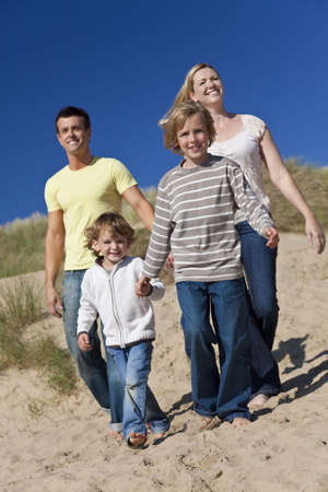 A happy family of mother, father and two sons, walking holding hands and having fun in the sand dunes of a sunny beach photo