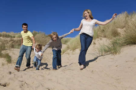 A happy family of mother, father and two sons, running holding hands and having fun in the sand dunes of a sunny beach photo