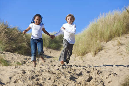A young mixed race African American girl and a little blond boy running, holding hands and having fun in the sand dunes of a sunny beach photo