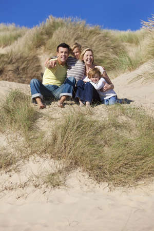 A happy family of mother, father and two sons, sitting and having fun in the sand dunes of a sunny beach Stock Photo - 8119105
