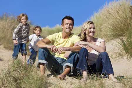 A happy family of mother, father and two sons, sitting and having fun in the sand dunes of a sunny beach Stock Photo - 8119098