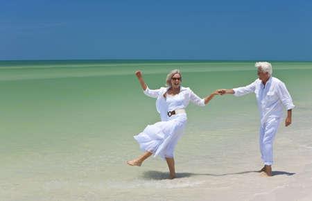 vestidos antiguos: Feliz los pareja hombre y mujer senior bailar y celebrar las manos sobre una playa tropical desierta con brillante cielo azul claro
