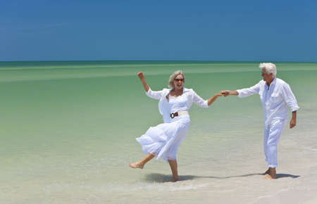 happy old people: Happy senior man and woman couple dancing and holding hands on a deserted tropical beach with bright clear blue sky